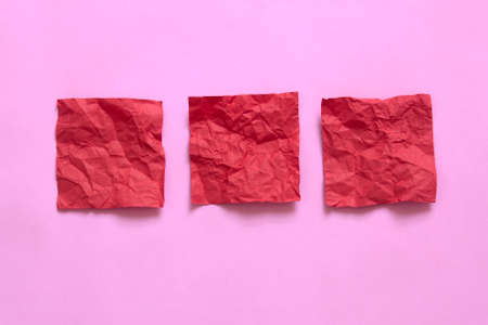 red crumpled sticky note papers on pink background