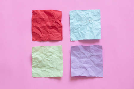 four crumpled note paper on pink background Standard-Bild