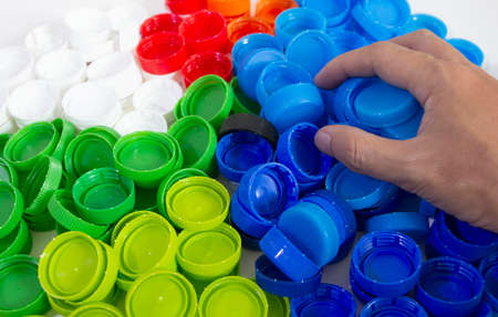 pile of many color recycle plastic bottle caps, recycle plastic bottle in hand