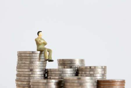 small figure businessman on stack of coin 免版税图像