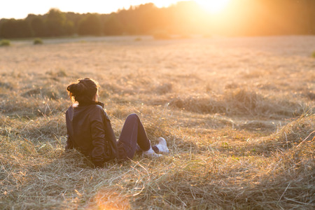 Portrait of a beautiful young woman or girl on meadow watching the sunset enjoying nature summer evening outdoors. Soft red light. Sunshine.