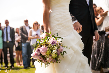 outdoor event: Moment in wedding,  bride and bridegroom holding hands with bouquet and wedding guests in background