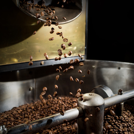 The freshly roasted coffee beans from a coffee roaster being poured into the cooling cylinder. Frozen moment. photo