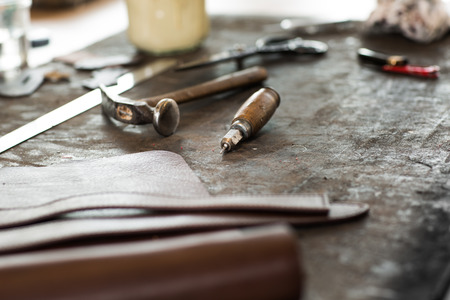 Leather crafting tools on working desk with a low depth of field Standard-Bild