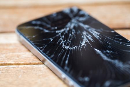 スマート フォン、木製のテーブルの上のガラスの破片