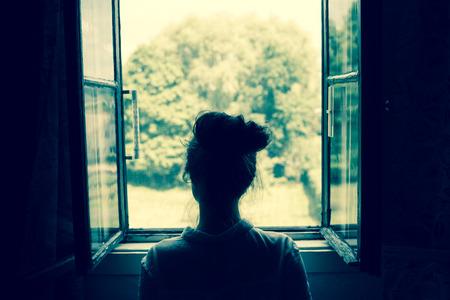 여자는 시골에서 정원이나 숲에 창을 통해 찾고. 빈티지 필터. 블루 톤.