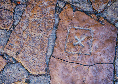 x marks the spot: X mark carved in stone pavement.