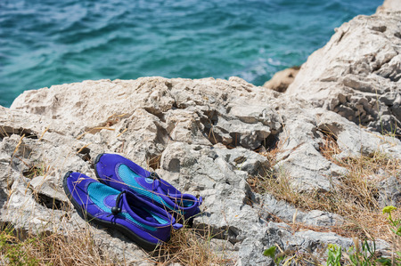 water shoes: Pair of violet water shoes on the rocks on coast of the sea.