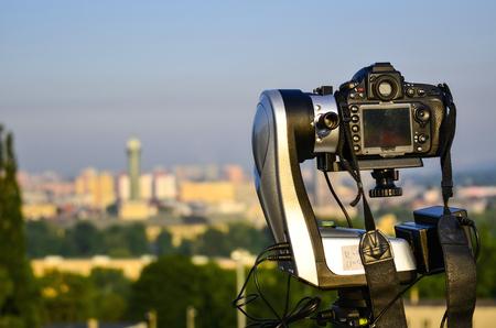 Camera fixed on automatic panorama head with out of focus city in background Reklamní fotografie