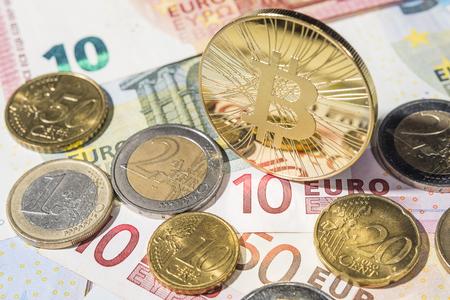 BTC Bitcoin munten ot top van stapel euro en eurocent munten en euro bankbiljetten.