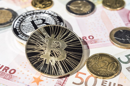 BTC Bitcoin coins ot top of pile of Euro and euro - cent coins and Euro bank notes.