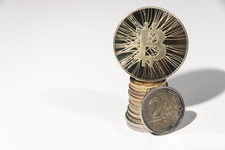 BTC Bitcoin coin ot top of pile of Euro and euro - cent coins on  white background.