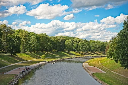 River Ostravice flowing trough park in Ostrava city with people enjoying summer on river bench. Archivio Fotografico