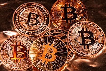 Shining metal BTC bitcoin coins in gold tint. Stock Photo