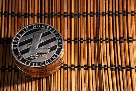 Shining metal LTC Litecoin coins on wood mat.