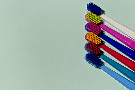 New unused colorful professional soft toothbrushes with lot of bristles in straight cut in a line on light blue background.