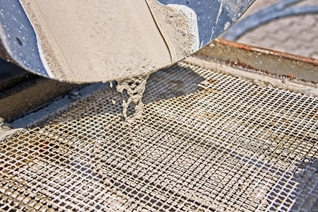 Close up of concrete pouring from truck into metal grid. Archivio Fotografico - 115168167