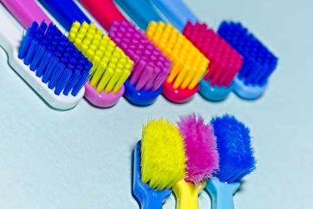 Used and new colorful professional soft toothbrushes with lot of bristles in straight cut in oppositing lines on light blue background. Archivio Fotografico - 115168180
