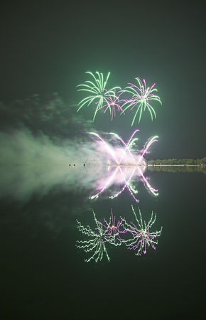 Colorful firework on the night sky with shimmering water reflection on lake. Archivio Fotografico - 115168195