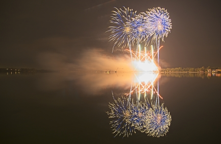 Colorful firework on the night sky with shimmering water reflection on lake. Archivio Fotografico - 115168298