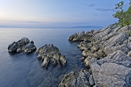 Rock shore of east Istria, Croatia in the morning just before sunrise. South- east direction. Archivio Fotografico - 115168772