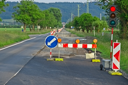 Countryside straight tree alley road reconstruction with red light and barrier Archivio Fotografico - 115168779