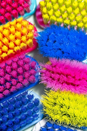 Full frame of used and new colorful professional soft toothbrushes heads with lot of bristles in straight cut on light blue background. Archivio Fotografico - 115168816