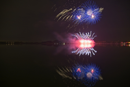 Colorful firework on the night sky with shimmering water reflection on lake. Archivio Fotografico - 115168923