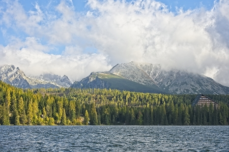 High Tatras mountains peaks in clouds from Strbske Plesolake  waterfront. Sun lit forest, snow covered rocky peaks and iconic mountain hotel. Archivio Fotografico - 115168933
