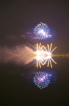 Colorful firework on the night sky with shimmering water reflection on lake. Archivio Fotografico - 115169132