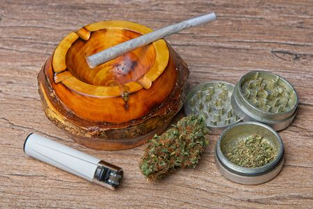 Close up of cannabis - marijuana bud and accessories - grinder, wooden ashtray, lighter and rolled joint - splif. Zdjęcie Seryjne