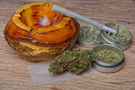 Close up of cannabis - marijuana bud and accessories - grinder, wooden ashtray, rolling paper and rolled joint - splif.