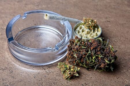 Close up of cannabis - marijuana buds and accessories - grinder, glass ashtray and rolled joint - splif. Zdjęcie Seryjne