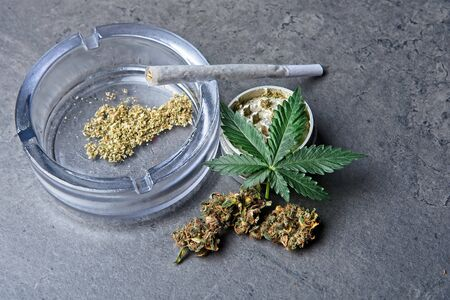 Close up of cannabis - marijuana buds, leaf and accessories - grinder, glass ashtray and rolled joint - splif.