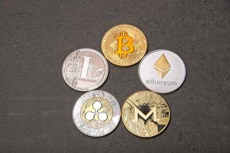 Shining gold and silver metal BTC Bitcoin, LTC litecoin,  ETH Ethereum, XRP Ripple and Monero virtual currency coins on grey background