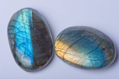 Two green blue and yellow rounded Labradorite crystal stone isolated on light background Stock Photo