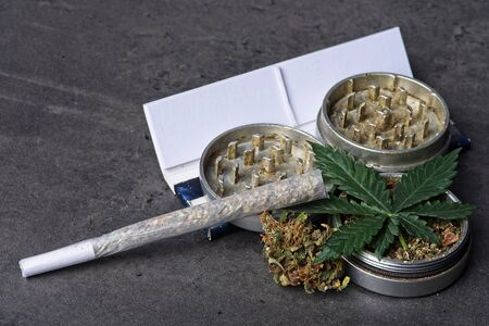 Close up of cannabis - marijuana buds, leaf and accessories - grinder, rolling papers and rolled joint - splif. Stock fotó