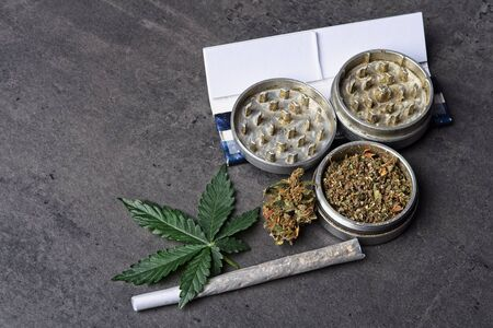 Close up of cannabis - marijuana buds, leaf and accessories - grinder, rolling papers and rolled joint - splif. Stockfoto