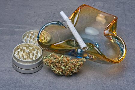 Close up of cannabis - marijuana bud and accessories - grinder, glass ashtray and rolled joint - splif. Stockfoto