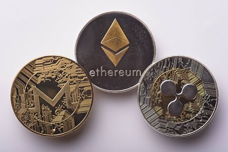 Shining gold and silver metal ETH Ethereum, Monero and XRP Ripple virtual currency coins on grey background