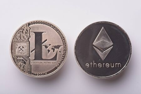 Shining silver metal ETH Ethereum and LTC Litecoin virtual currency coins on white background
