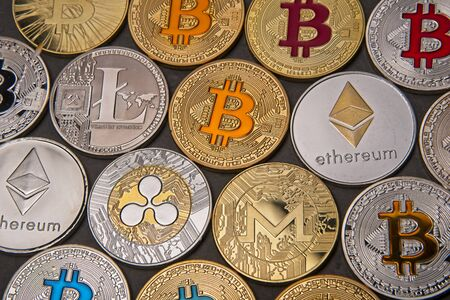 Full frame of shining gold and silver metal BTC Bitcoin, LTC litecoin,  ETH Ethereum, XRP Ripple and Monero virtual currency coins on grey background