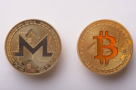 Shining gold metal Monero and BTC Bitcoin virtual currency coins on white background Zdjęcie Seryjne - 129331290