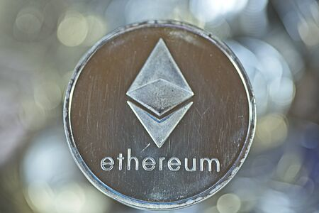 Shining silver metal ETH Ethereum virtual currency coin on shimmering background