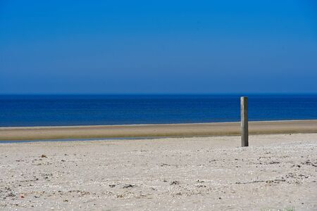 Blue see horizon on sandy beych with wood pole on the beach by  Hondsbossche Zeewering coastal barrier at Netherlands coast