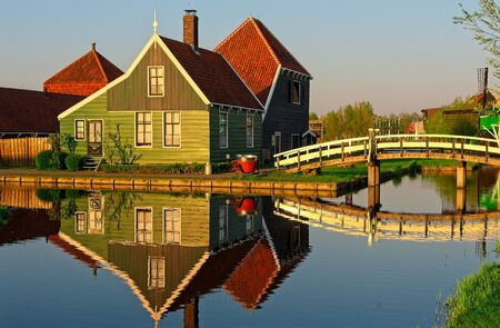 Old Dutch industrial house in setting sun light at Zaanse Schans at spring reflecting in calm water. Archivio Fotografico