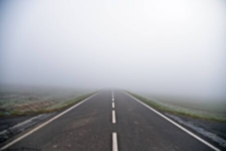 Intentionaly blurry - defocused photo of straight empty country road leading into morning fog / mist in the center usable for background.