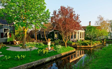 Old Dutch house in setting sun light at Zaanse Schans at spring reflecting in calm water.