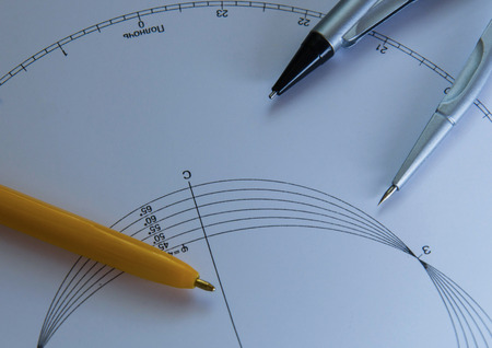 Compasses and pen on the white paper photo