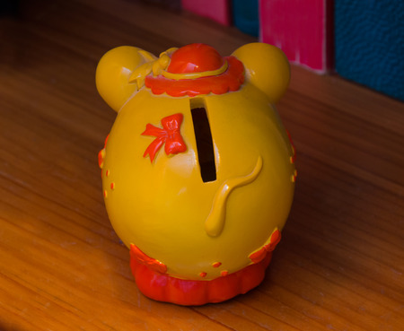 path to wealth: A yellow mouse as moneybox on the home table